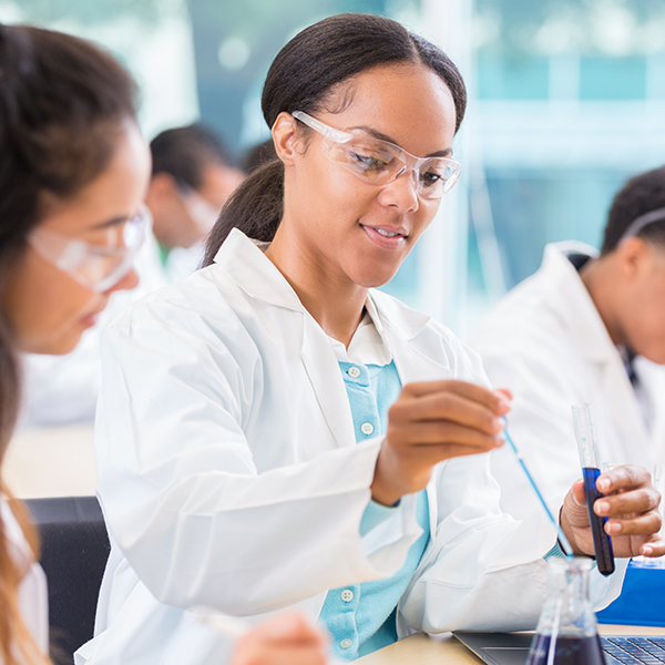 African American female chemist drops liquid into a beaker. Her assistant is watching her. She is recording the findings on a laptop.
